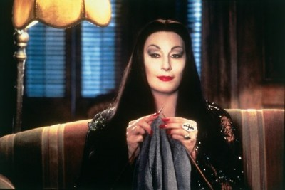 Still from The Addams Family showing Morticia knitting